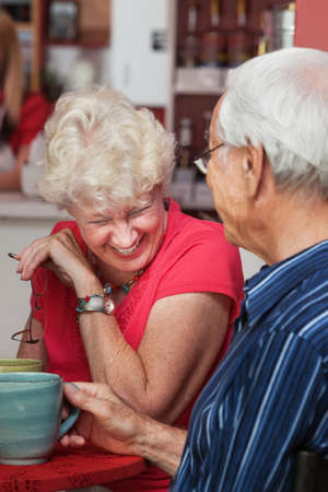Older Caucasian woman laughing at table with man