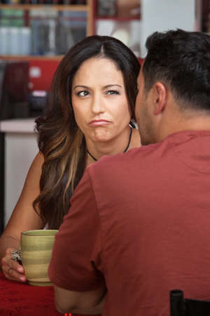 Doubtful woman looking at man sitting in cafe