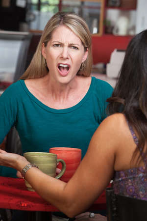 Outraged European woman across from person in a coffeehouse