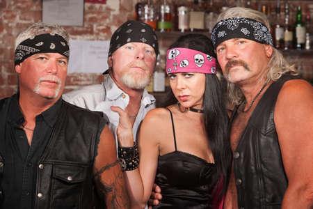 Tough male biker gang members with beautiful woman