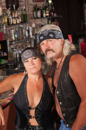 Attractive middle aged biker couple with bandannas in bar