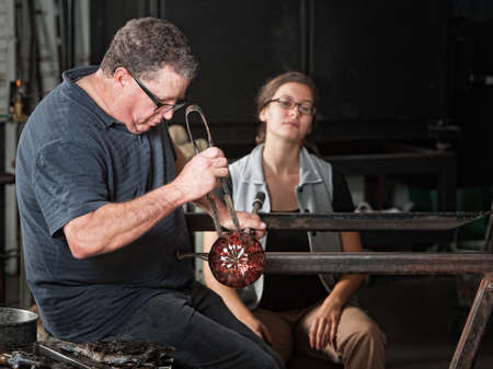 Photo pour Student watching European glass artisan work on a round vase - image libre de droit