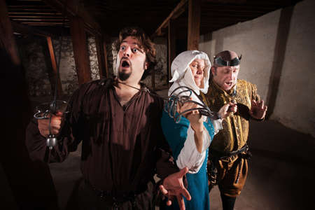 Brave middle ages nun with weapons on two men