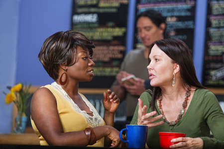 Pair of calm women in conversation at coffee house