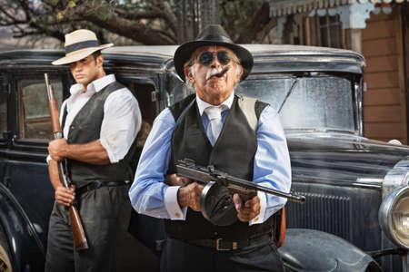 Serious mob boss with gun and guard near car
