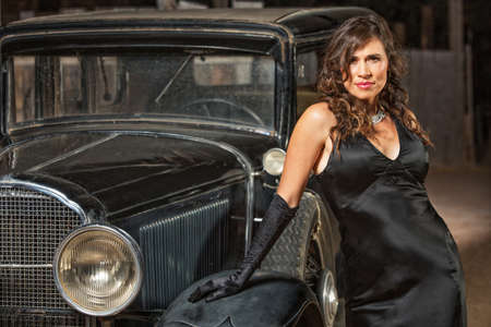 Seductive woman in black leaning on antique automobile