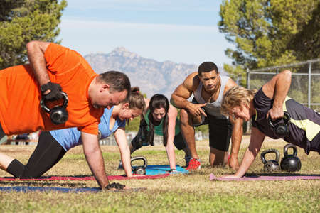 Male instructor training mature adults in boot camp fitness