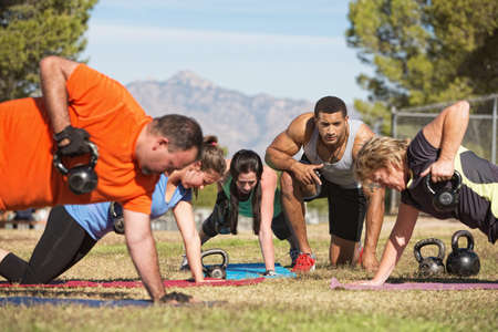 Foto de Fitness instructor with people exercising in outdoor bootcamp - Imagen libre de derechos