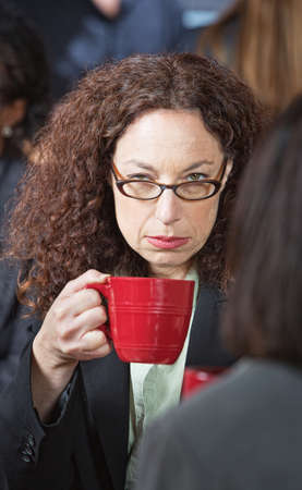 Offended businesswoman with friend holding coffee cup