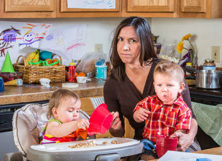 Photo for Stressed out mother in kitchen with her babies - Royalty Free Image