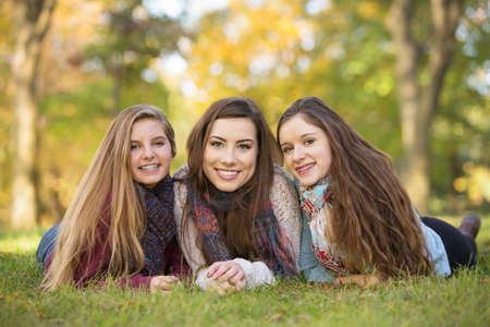 Three happy Caucasian teen girls sitting together