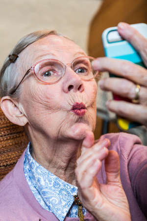 Happy elder woman taking duck face selfie