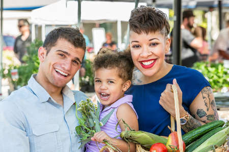 Smiling family with basket of produce at farmers market