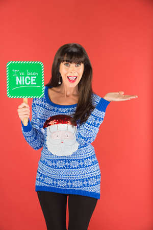 Happy single woman in tacky blue sweater holding nice sign over red background