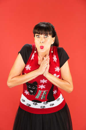 Front view on single woman in garish Christmas sweater with palms together over red background