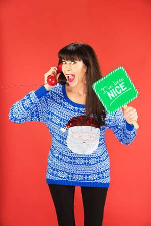 Excited woman on phone holding sign about nice behavior over red