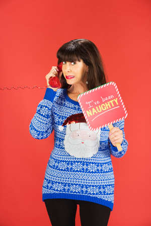 Ashamed adult woman in ugly blue sweater with naughty sign on phone