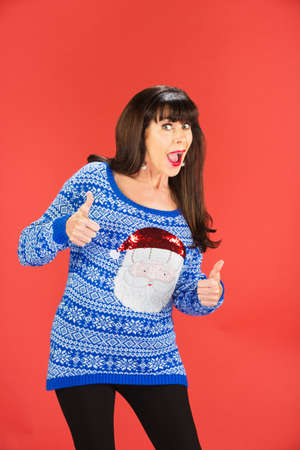 Excited single woman in tacky Christmas sweater with thumbs up over red background