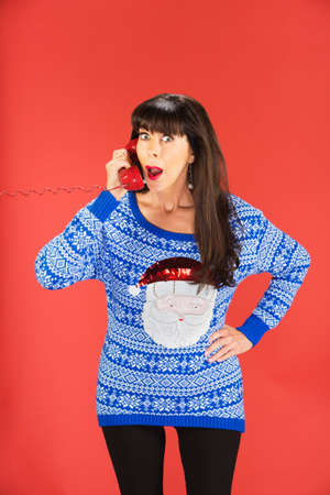 Surprised woman in ugly blue Santa Claus sweater with surprised expression on red telephone