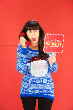 Shocked woman in ugly Santa sweater holding phone and naughty sign over red background
