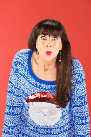 Cute single woman in gaudy Santa Claus sweater puckering lips over red background
