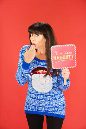 Beautiful embarrassed woman in gaudy sweater holding naughty sign while keeping hand near mouth