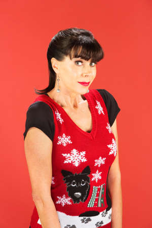 Front view on grinning woman wearing ugly Christmas sweater over red background