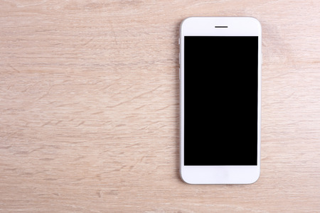 Photo pour Blank screen smartphone on wooden background - image libre de droit