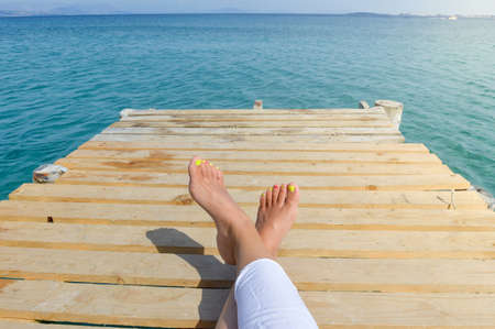 Womans legs on a dock while relaxing by the seaside