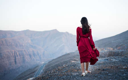 Photo pour Fashionable girl on a desert mountain top wearing red dress - image libre de droit