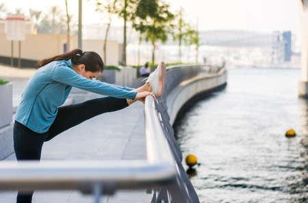Foto de Girl stretching with music before running in urban environment - Imagen libre de derechos