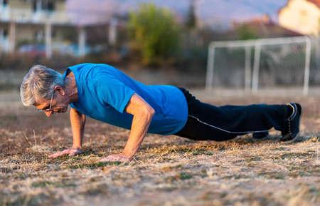 Foto de Senior Man doing pushups on an outdoor workout - Imagen libre de derechos