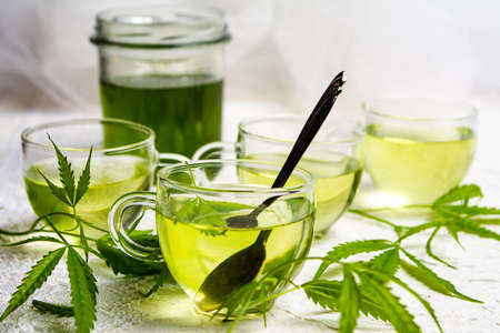 Photo pour Cannabis herbal tea served in glass teacups with marijuana leaves - image libre de droit