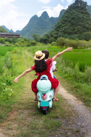 Photo pour Couple riding motorbike around rice fields of Yangshuo in China - image libre de droit