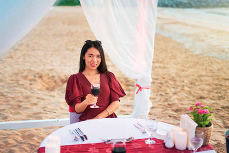 Photo for Woman having a glass of wine on romantic beach dinner in cabana - Royalty Free Image
