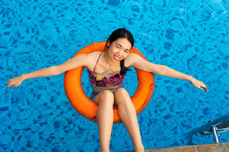 Photo pour Girl enjoying at the swimming pool floating on water - image libre de droit