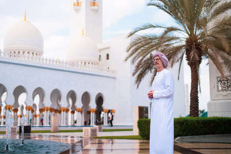 Photo pour Arab man visiting the Grand Mosque in Abu Dhabi wearing kandora - image libre de droit