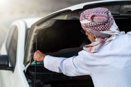 Photo pour Senior Arab man fixing his car outdoors - image libre de droit