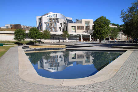 Front view of the Scottish parliament with the modern design reflected in the water feature at the front of the building.