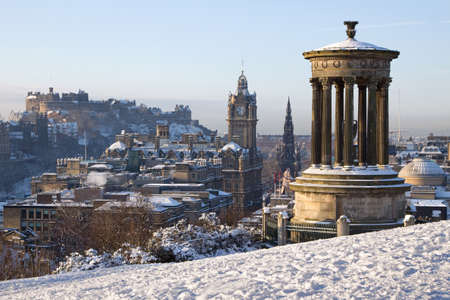Edinburgh winter city view captured from Calton Hill with the Dugald Stewart monument in the foreground and the castle, Scott monument and Balmoral clock tower in the background.