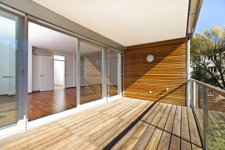 Sunlit balcony with wooden floor and wall of an architectural contemporarily apartment building in green area