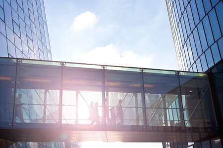 Foto de Silhouettes of unrecognizable business people using a transition of a contemporary office building. - Imagen libre de derechos