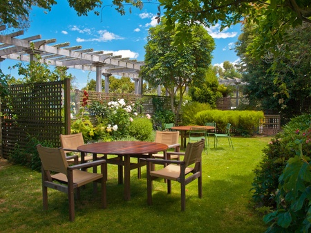 a wooden dining table set in lush garden setting