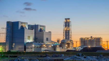 Photo pour Ultra modern coal powered electrical power plant during sunset under a blue and orange sky - image libre de droit
