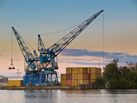 Two cranes are waiting for cargo te export in a dutch harbor in Rotterdam, Netherlands