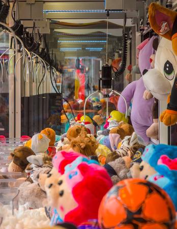 Claw crane with soft cuddly toys in an arcade machine