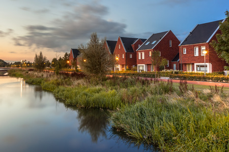 Photo pour Long exposure night shot of a Street with modern ecological middle class family houses with eco friendly river bank in Veenendaal city, Netherlands. - image libre de droit