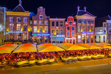 Foto de GRONINGEN, THE NETHERLANDS-MAY 5,2015: Students on teracces in the night. Famous bars and restaurants in the old center of the university town of Groningen. The Grote Markt is famous for its nightlife for students - Imagen libre de derechos