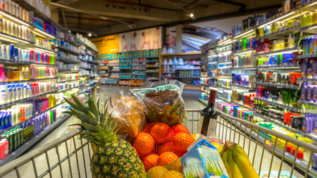 Photo pour Easter shopping Grocery cart at a colorful supermarket filled up with food products as seen from the customers point of view - image libre de droit