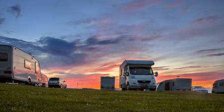 Photo for Caravans and cars parked on a grassy campground in summer under beautiful sunset - Royalty Free Image